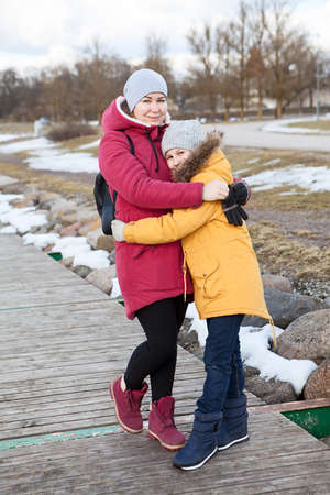Mother embracing her frozen daughter, adult woman and young girl standing on quay at winter cold weather, people dressed warm clothes 免版税图像