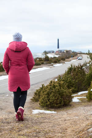 Rear view at woman dressing warm red coat standing on hill and looking at lighthouse on sea cape, travel at winter season 免版税图像