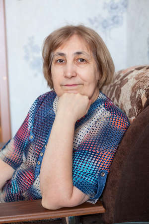 Portrait of mature woman sitting in armchair with her head propped on hand and looking at camera, indoors