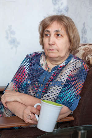 Caucasian mature woman holding tea cup, sitting in armchair in a domestic room