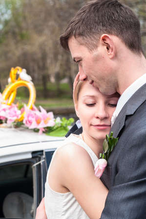 Calm and tender bride is in bridegroom hug, Caucasian newlywed couple portrait, woman with closed eyes
