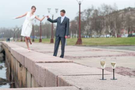Newlywed couple walking on embarkment, two stem glasses with champagne standing on granite quay 免版税图像