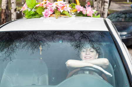 Smiling bride looking through the windshield while sitting on driver seat in car, holding steering wheel