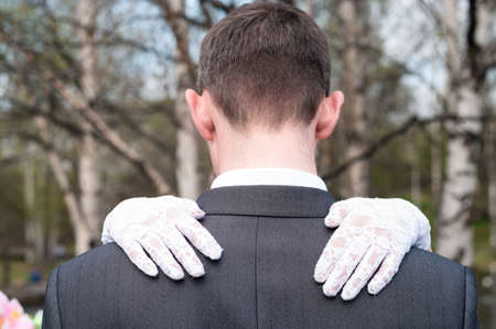 Bridal hands wearing white gloves lying on men shoulders, a newlywed couple, rear view 免版税图像