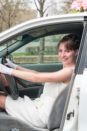 Smiling bride wearing white dress and gloves sitting on driver seat in car, holding steering wheel, opened doors