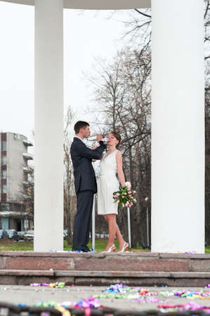 Bridal pair drinking champagne from wine glasses, bride and groom are between white columns outdoors