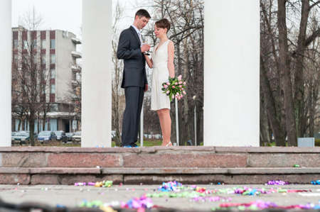 Caucasian bridal pair cheers and clink wine glasses with champagne, bride and groom are between white columns outdoors