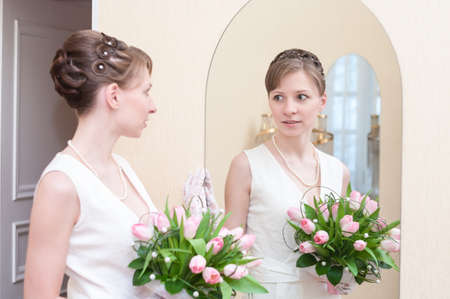Young Caucasian woman in white dress standing opposite the mirror with wedding bouquet