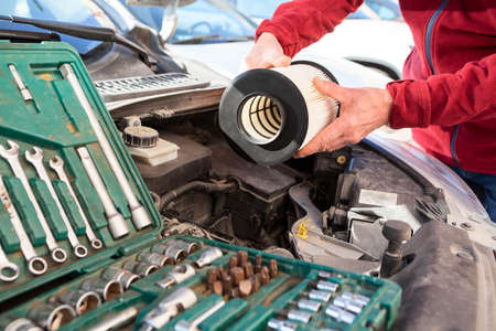 New cartridge of air filter, male hands installing maintenance item, close-up view