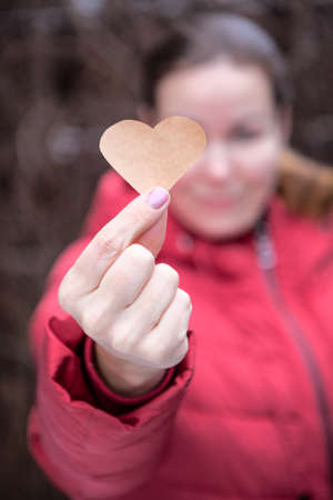 Attractive Caucasian woman wearing warm red jacket is outstretched hand wit a paper heart