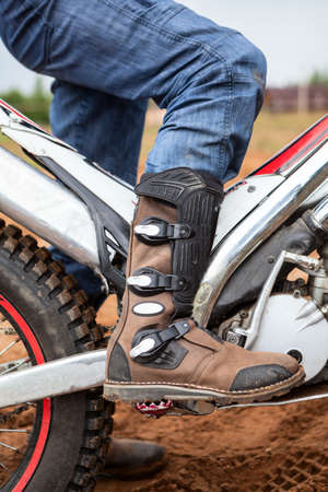 Close up view of motocross boot standing on peg of trial motorcycle. Safety footwear and apparel for a riding 免版税图像