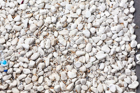 Cigarette butts are in pebbles, small parts of a cigarette that is left after smoking, background