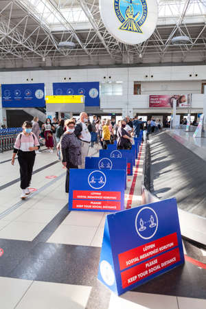Dividing boards are placed in the Antalya International airport due pandemic. Signs with notification about keeping social distance during Covid-19 pandemic Antalya, Turkey 新闻类图片