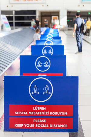 Plastic boards are in luggage area in the Antalya International airport. Signs with notification about keeping social distance during Covid-19 pandemic. Antalya, Turkey