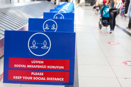 Antalya, Turkey-circa Oct, 2020: Separating boards are in luggage area in the Antalya International airport. Signs with notification about keeping social distance during Covid-19 outbreak