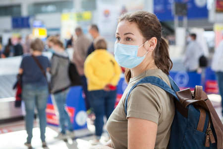 Caucasian woman wearing medical mask waiting her luggage in an international airport area 免版税图像