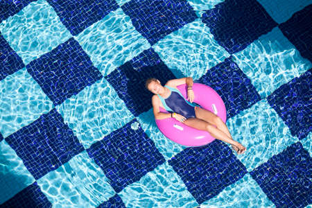 Teenage girl swimming in pool with inflatable ring, top view