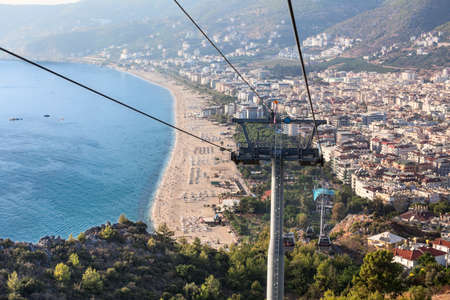 Mountain ropeway connects city and Alanya castle, cityscape from the cabin of cableway with Kleopatra beach. The Alanya, Turkey 免版税图像