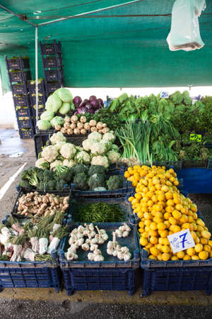 Lemons, garlic, cabbage and other green vegetables are in plastic boxes on sale. Fruit and vegetable marketplace is in the Alanya, Turkey