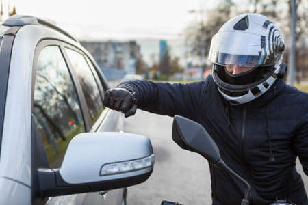 Motorcyclist beat side view mirror of car with a fist, conflict is on the road 免版税图像