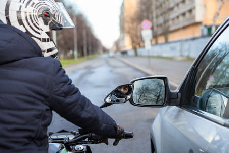 Motorcyclist stands by side with car on the road, lateral rear mirrors are close to each other, touching during movement
