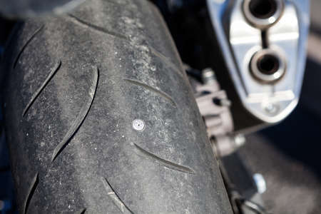 Screw nail puncturing motorcycle tire. Close-up view at rear wheel 免版税图像