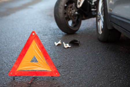 Emergency warning triangle positioned on asphalt road due accident with motorcycle and car
