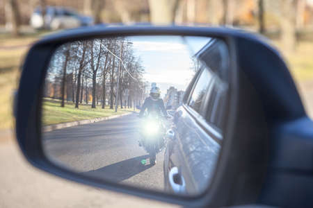 Dazzle lighting from riding motorcycle in side view mirror of a car. Dazzling effect concept
