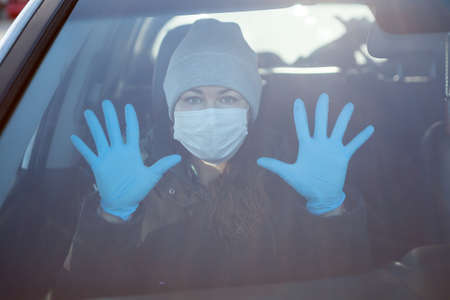 Woman a passenger showing hands in blue rubber gloves, individual preventive measures during coronavirus including medical mask