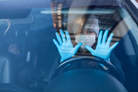 Woman a driver showing her hands in blue rubber gloves, individual preventive measures during the coronavirus