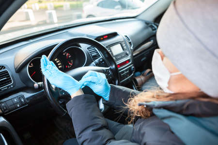 Female driver puts on rubber gloves for protect herself from bacteria and virus while driving her car. Coronavirus prevention
