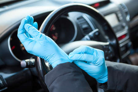 Driver getting his blue protective gloves before touching a steering wheel. Protection against the Covid-19 virus