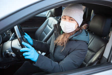 Woman a driver in blue rubber gloves and safety mask ready for driving a car, individual preventive measures during coronavirus