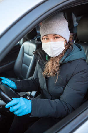 Woman a driver in blue protective gloves and safety mask ready for driving car, individual preventive measures during COVID-19