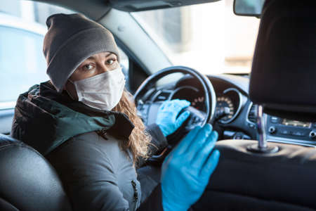 Woman looking back while sitting on the driver seat inside car in facemask and blue gloves, personal hygiene