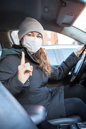 Adult driver in medical mask gesturing with forefinger before driving a car. Notice to wearing mask anywhere
