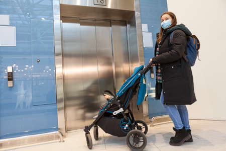 Mother wearing face mask waiting elevator with children pram in hall of a shopping mall Banque d'images