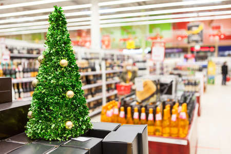 Christmas tree against pepartment of the supermarket selling alcoholic beverages. The December sales