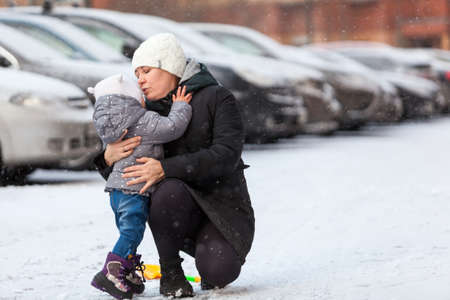 Mother talking with her little child, embracing and kissing after falling dawn on ice at winter season, urban street