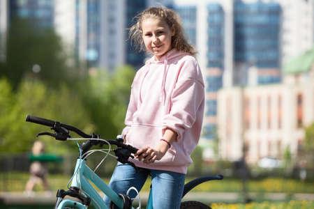 Blond Caucasian teenage girl sitting on her blue bicycle, portrait outdoor Foto de archivo