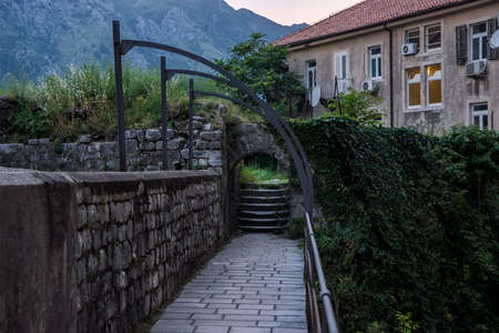 Evening view of the village, ladder, of the stone wall twined a rod and fence. Against the background of high mountains Stock Photo