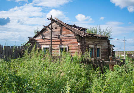 damaged roof: Old wooden dilapidated rural house stands in a thicket of bushes and grass. Abandoned building.