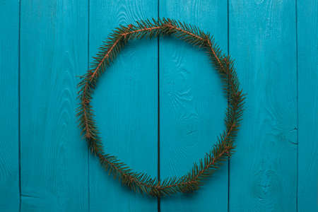 Fluffy wreath. A wreath from Christmas tree branches on wooden Board. A wreath of fir. New year symbol on blue background.