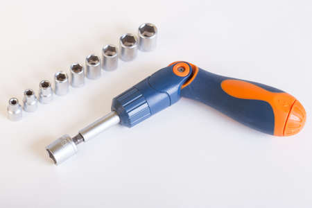 Top view of the screwdriver head. A set of heads and a screwdriver on a light background. Screwdriver with blue - orange handle and a set of heads under the nut. Stock Photo