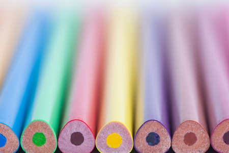 Colored pencils in a blurred form. The image is blurred. A set of colored pencils. Selective focus. A place for a label.