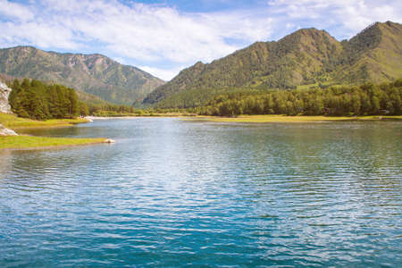 A beautiful lake with mountains in the background. The magnificent scenery of the Altai mountains in Sunny weather. Reservoir Chemal hydroelectric power station Stock Photo