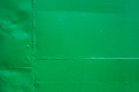 The green background. Painted metal surface. The surface of the train as a background element. Metal painted green. Iron plates welded together