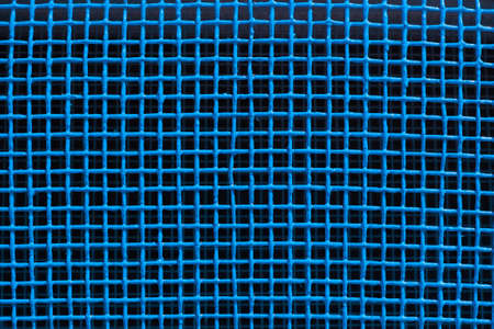 Cell a blue grid. Blue background. Painted metal surface. Texture ventilation grid as a background element. Metal painted in blue color. The intersection of the lines. Squares.