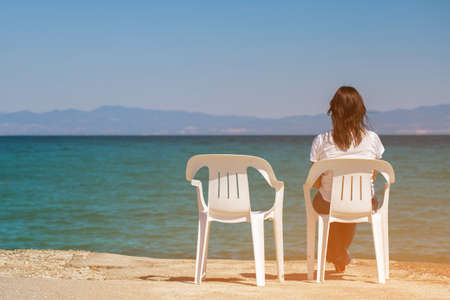 Girl sitting on white chair near the blue sea. Woman looking into the distance beyond the horizon. Lonely man by the sea.  Stock Photo