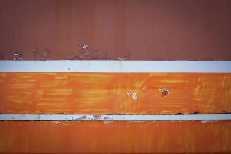 A dark stripe on the orange. The old orange background. Painted metal surface. The metal is painted orange. White stripe on an orange background. Peeling paint on the surface of railway car